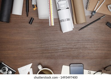 Creative flat lay of architects wooden table with roll blueprints, architectural project plan, engineering tools, office supplies, Workspace for designer concept