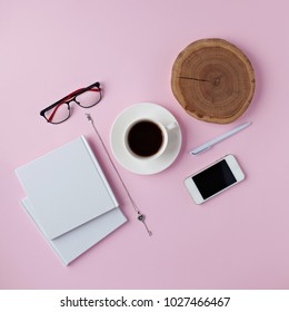 Creative flat lay arrangement with cup of cofee, notebook, mobile phone, branch on pink background. Top view workspace.