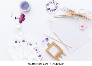 Creative flat lay art workspace with yellow palettes, paint brushes,. Artist background