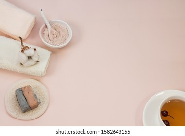 Creative flat lay of bath accessories, beauty spa concept with copy space, handmade soap, rose and clay cleansing face  mask, top view, cup of healthy rosehip tea, pink background