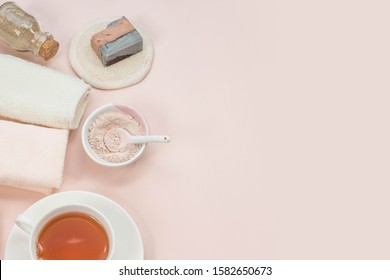 Creative flat lay of bath accessories, beauty spa concept with copy space, handmade soap, rose and clay cleansing face  mask, top view, cup of natural tea, pink background