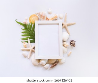 creative flat lay of beach and sea in summer holiday beach background with shells and white picture frame with copy space.