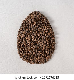 Creative flat lay composition with easter egg shape made of coffee roasted beans.Pastel colors and soft shadows. Realistic aesthetic look. Contemporary style.