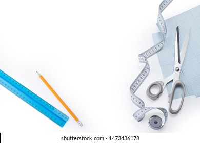 Creative flat lay composition of measuring tape, stainless steel sewing scissors, graph paper, ruler and pencil on a white background