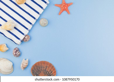 Creative flat lay concept of summer travel vacations. Top view of beach towel and seashells and starfish on pastel blue background with copy space in minimal style, template for text