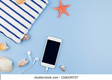 Creative flat lay concept of summer travel vacations. Top view of beach towel, seashells, starfish and smartphone on pastel blue background with copy space in minimal style, template for text