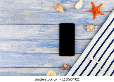 Creative flat lay concept of summer travel vacations. Top view of beach towel smartphone seashells starfish on pastel blue wooden planks background with copy space mockup template for text