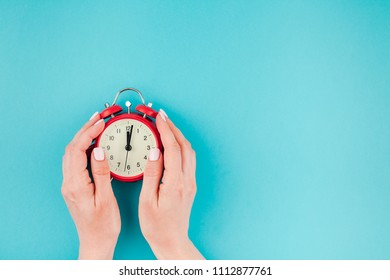 Creative flat lay concept top view of woman hands holding the red vintage alarm clock on bright blue turquoise color paper background with copy space in minimal style, template for text