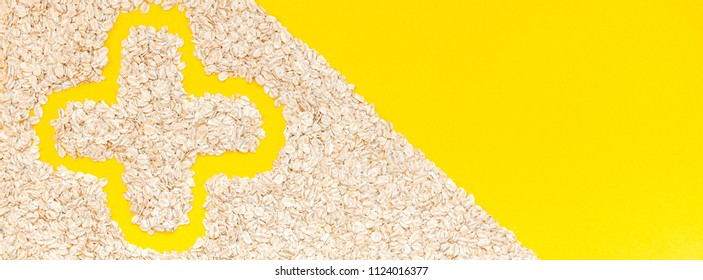 Creative flat lay concept top view of oatmeal flakes for healthy and vegetarian organic food for breakfast on a bright yellow color paper long wide banner with copy space in minimal style