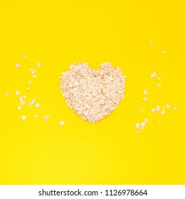 Creative flat lay concept top view of oatmeal flakes for healthy and vegetarian organic food for breakfast on a bright yellow color paper background with copy space in minimal style, square template