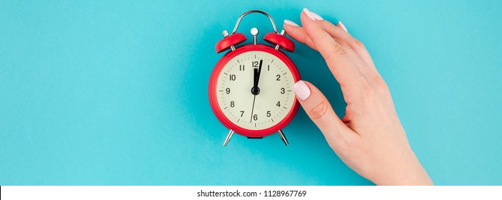 Creative flat lay concept top view of woman hand holding the red vintage alarm clock on bright blue turquoise color paper background with copy space in minimal style, long wide banner