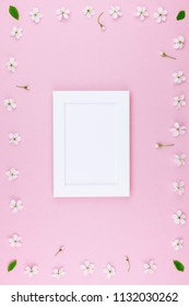 Creative flat lay concept top view of blank frame mock up and cherry tree flowers on pastel millennial pink background with copy space in minimal style, template for lettering, text or design