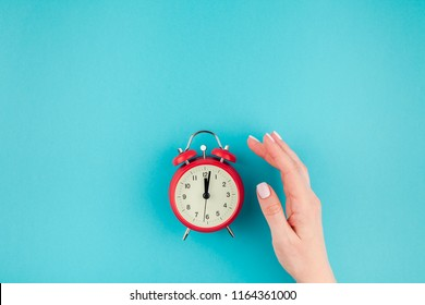 Creative flat lay concept top view of woman hand holding the red vintage alarm clock on bright blue turquoise color paper background with copy space in minimal style, template for text