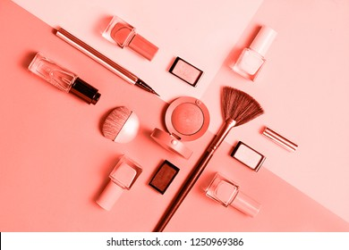 Creative flat lay of fashion bright nail polishes and decorative cosmetic on a colored in color of year 2019 Living Coral background. Macro color 16-1546 background. Beauty blogger concept. Top view