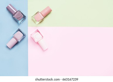 Creative flat lay of fashion bright nail polishes on a colorful background. Minimal style. Copy space. Beauty blogger concept. Top view.