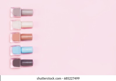 Creative flat lay of fashion bright nail polishes on a colorful background. Minimal style. Copy space. Beauty blogger concept. Top view