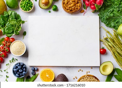 Creative flat lay with healthy vegetarian meal ingredients and white marble cutting board. Raw food concept with copy space. A variety of organic fruits, nuts, vegetables with avocado. Vegan menu