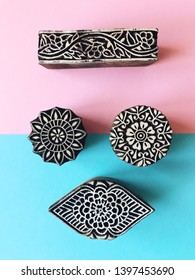 Creative Flat lay kalamkari wooden stamps on pastel color background. Blue and pink pastel color paper geometric flat lay background with indian kalamkari stamps. Top view printing blocks. Funny face