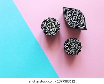Creative Flat lay kalamkari wooden stamps on pastel color background. Blue and pink pastel color paper geometric flat lay background with indian kalamkari stamps. Top view printing blocks