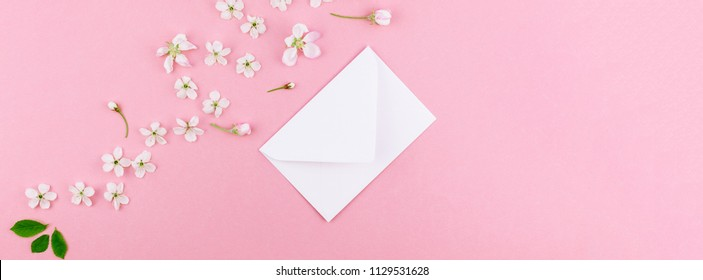 Creative flat lay long wide banner of blank letter envelope and spring cherry tree flowers on millennial pink background with copy space in minimal style, template for celebration, valentine cards