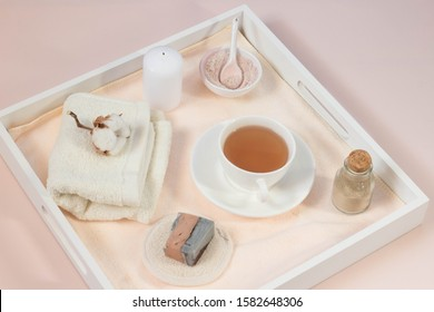 Creative flat lay made of bath accessories, beauty spa concept with copy space, handmade soap, rose and clay cleansing face  mask in square wooden box top view, cup of natural tea, pink background