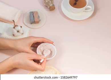 Creative flat lay made of bath accessories, beauty, spa concept with copy space, woman hands apply rose and clay mask in bowl, handmade soap, cup of tea,  top view.