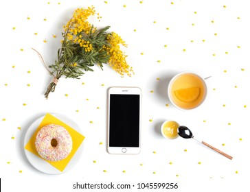 Creative flat lay with mobile phone mockup, bouquet of mimosa flowers, donut, tea and honey. Floral pattern isolated on white top view, copy space. Feminine desk with accessories.