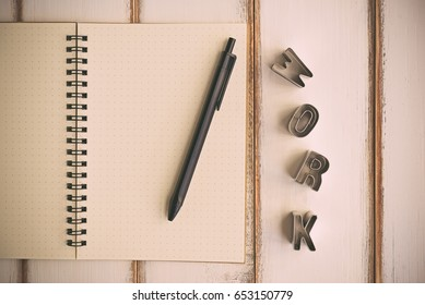 Creative flat lay mockup design of workspace desk with WORK Wording - Alphabet cookie cutters on the blank notebook with black pen . Business Concept. (Vintage Style)