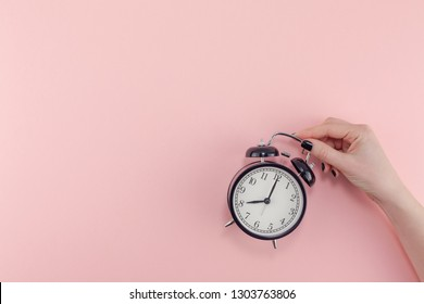 Creative flat lay morning time emotions concept top view of woman hand holding black vintage alarm clock pastel millennial pink color paper background with copy space minimal style template for text