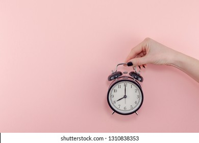 Creative flat lay morning time emotions concept top view of woman hand holding black vintage alarm clock, pastel millennial pink color paper background with copy space, minimal style template for text.