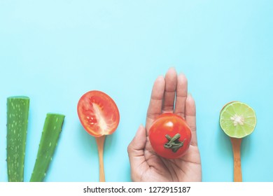 Creative flat lay of natural beauty concept, alovera, lime and tomato on woman's hand, Health and skincare ingredients