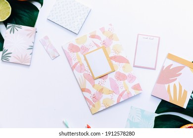 Creative flat lay on white background. Summer Office desk table with notepad, supplies and fresh fruits. Top view with copy space, flat lay