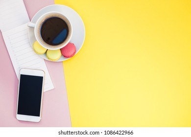 Creative flat lay photo of coffee cup with macaroons and a notepad with copy space on pink and yellow background minimal style