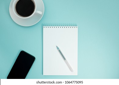 Creative flat lay photo of workspace desk with paper notebook, smartphone, earpieces, pen and coffee with copy space background minimal style