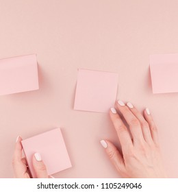 Creative flat lay photo of workspace desk with millennial pink sticker paper mocked up in woman hands holding and gluing them on wall with copy space background minimal style. Square Template