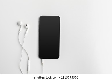 Creative flat lay photo of workspace desk with earphones and mobile phone
