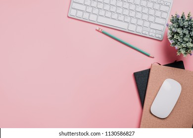 Creative flat lay photo of workspace desk with copy space. Pink desk with keyboard,pencil,mouse and note book.