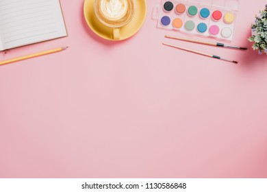 Creative flat lay photo of workspace desk. Pink desk with water colour,pencil,note book,paint brush and cup of coffee.