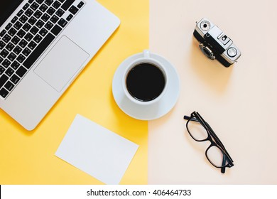 Creative flat lay photo of workspace desk with laptop, blank paper, coffee, eyeglasses and film camera on yellow modern background