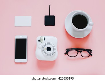 Creative flat lay photo of workspace desk with instant camera, coffee, tag, smartphone and eyeglasses on pink background, minimal and modern design with copyspace for background