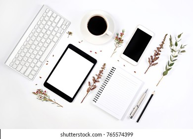 Creative flat lay photo of workspace desk with smartphone, tablet, keyboard, coffee and notebook on white background