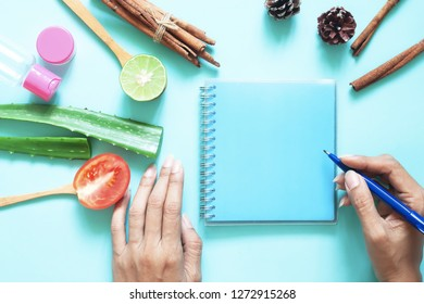 Creative flat lay of skincare and healthcare concept. Woman's hands with empty notebook, tomato, alovera, lime and cosmetic containers on pastel background