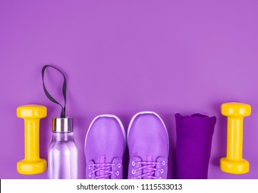 Creative flat lay of sport and fitness equipments with violet sneakers.