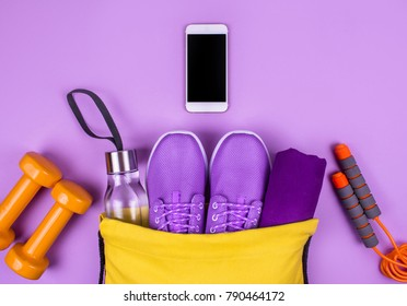 Creative flat lay of sport and fitness equipments on yellow background with copy space.