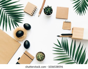 Creative flat lay stationery with black Easter eggs. Minimal work space