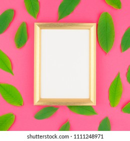 Creative flat lay top view pattern with fresh green leaves on bright pink square background with golden frame mock up and copy space in minimal pop art style, template for text