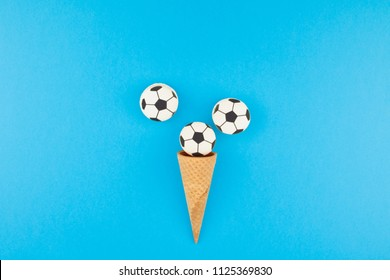 Creative flat lay top view of ice cream waffle cones with soccer balls macarons on bright bold blue background with copy space in minimal style, concept of football games for children birthday