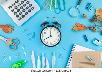 Creative flat lay top view back to school concept with alarm clock, color school and office supplies on bright turquoise paper table frame background with copy space, template for text or design