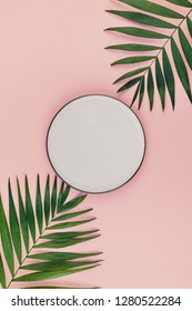 Creative flat lay top view of green tropical palm leaves millennial pink paper background with empty plate mock up copy space. Minimal tropical palm leaf plants summer template for your text or design