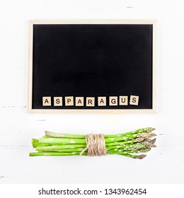 Creative flat lay top view mockup of fresh green asparagus with chalkboard frame on white wooden table background copy space